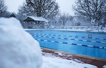 swimmers enjoy the heated water of Hampton Pool in the biggest snowfall in 18 years